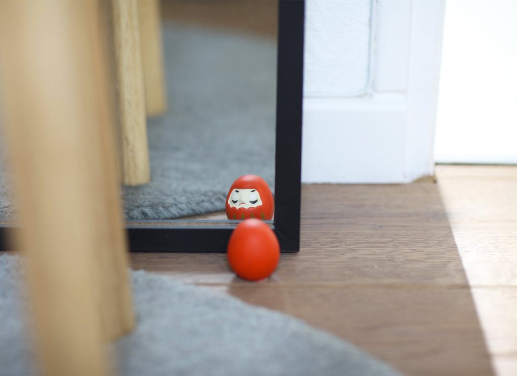 Japanese Daruma ou Bodhidharma looking into the mirror