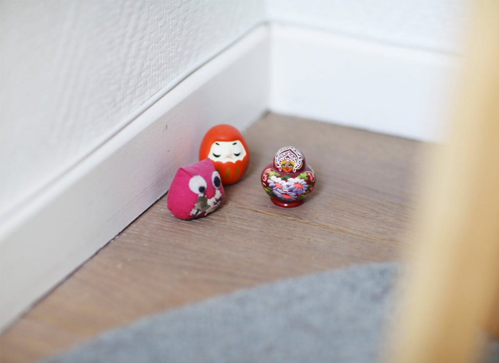 Small figurines: Japanese Daruma Bodhidharma, mini russian puppet and pink owl